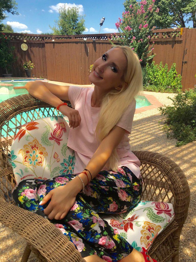Liliya lounging in floral pants, pink tee