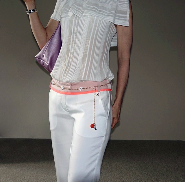 Close up of chain belt on narrow-legged white pants